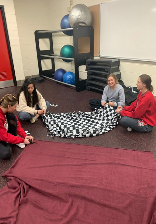 NHS members creating many blankets for the Adolescent & Young Adult Cancer Program